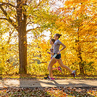 Photo of two students running in a park in front of trees with yellow leaves.