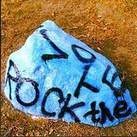 """Photo of the Macalester Rock, painted bright blue and reading """"ROCK THE VOTE."""""""