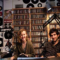 Photo of two students smiling in the Macalester radio station.