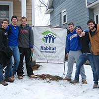 Photo of students posing with a Habitat for Humanity sign