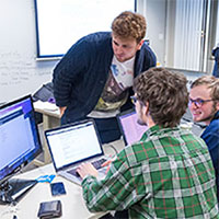 Photo of three students working together over a computer