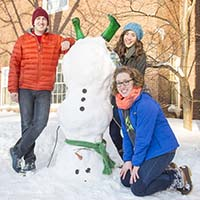 Photo of three students posing with an upside-down snowman
