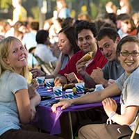 Photo of students smiling for the camera over a picnic