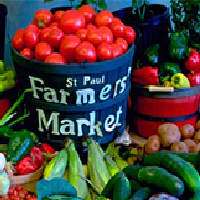 """Photo of a bucket of tomatoes reading """"St. Paul Farmers Market"""""""