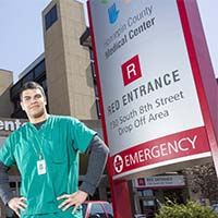 Photo of a student standing in front of Hennepin County Medical Center