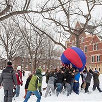 Photo of students pushing a ball outdoors in snow