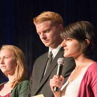 Photo of three students; one is holding a microphone