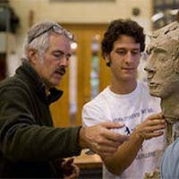 Photo of a student and a professor talking about the student's sculpture