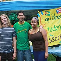 Photo of three students smiling in front of a poster for Caribbean Student Association