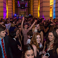 Photo of a crowd of students in formal wear dancing and talking