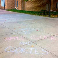 """Photo of a sidewalk with chalk on it reading """"APPLE CIDER AND COOKIES"""""""