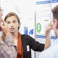 Photo of a student presenting a research poster