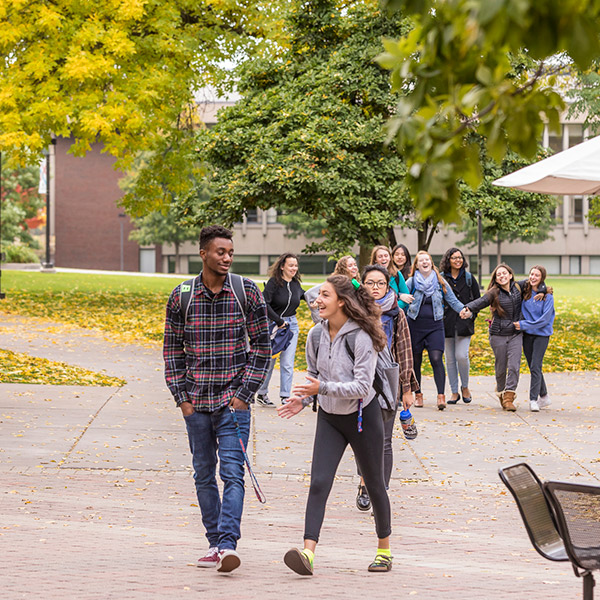 Students walking on campus in autumn.