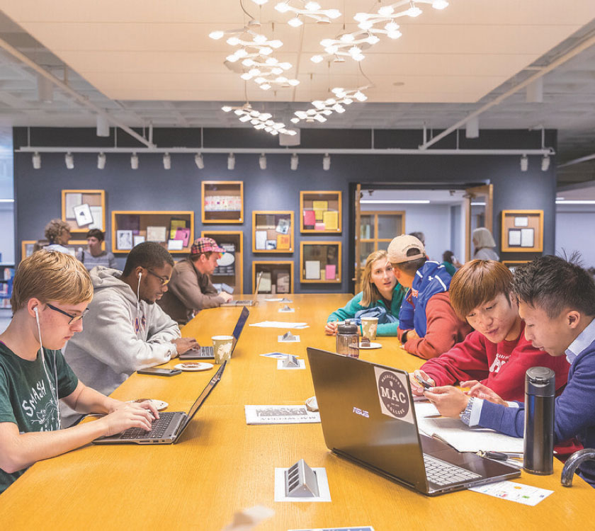 Students working on their laptops at a long table in the Library.