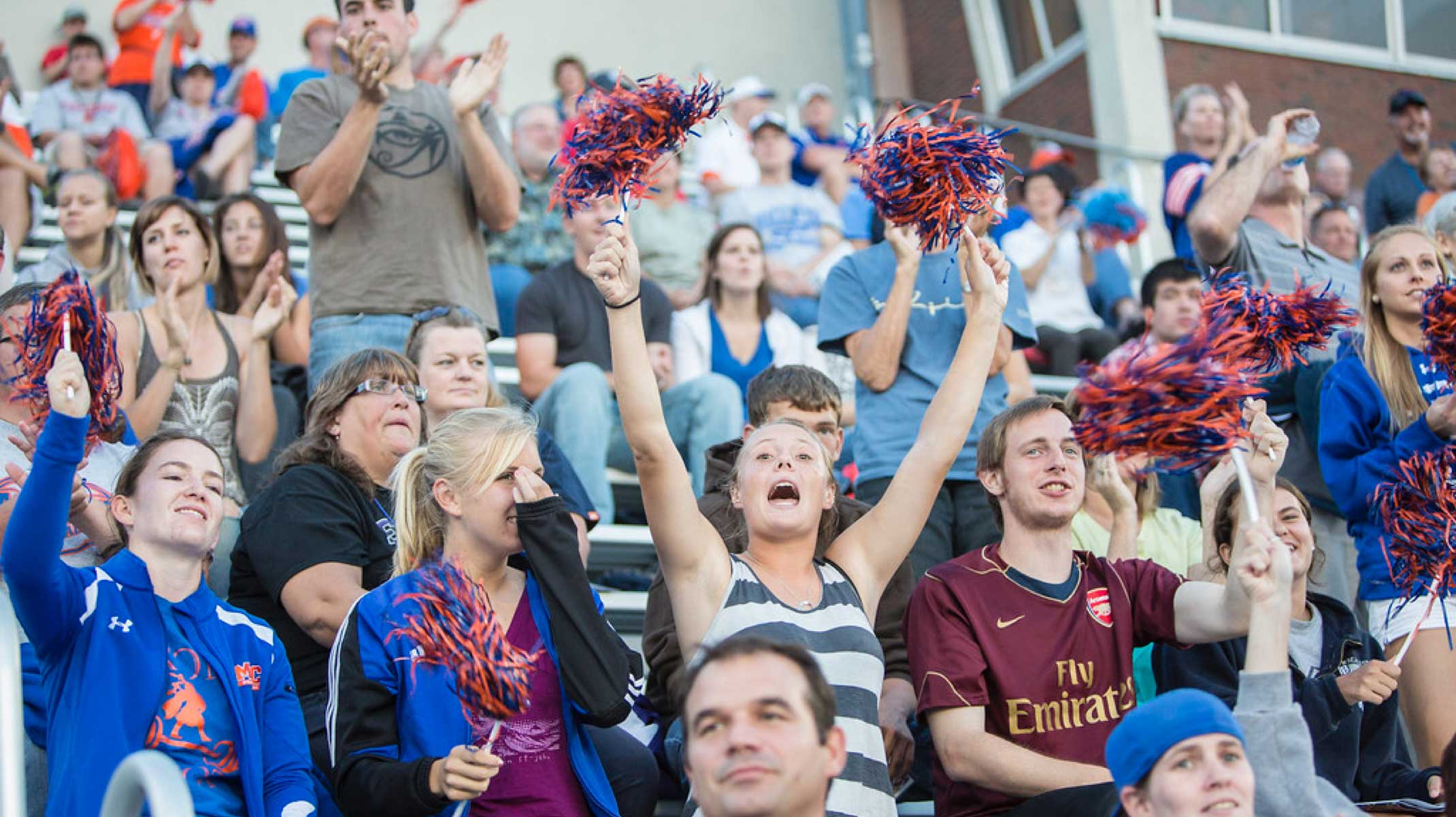 Macalester students cheering in the stadium stands.