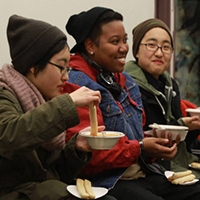 Photo of three students eating soup and talking