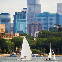 Photo of boats in Bde Maka Ska against the Minneapolis skyline