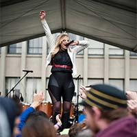Photo of a Springfest performer jumping up and down on stage
