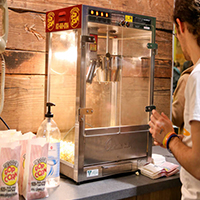 Photo of a student standing in front of a popcorn machine