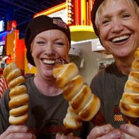 Photo of two women smiling and holding fried dough on a stick