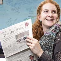 Photo of a student holding a copy of the Mac Weekly