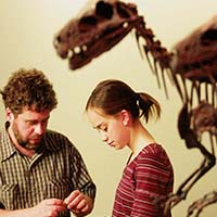 Photo of two people talking in front of a dinosaur skeleton