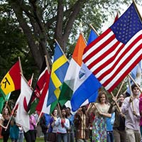 Photo of a line of students carrying flags representing their home countries