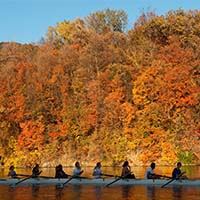 Photo of students rowing down a river on an autumn day