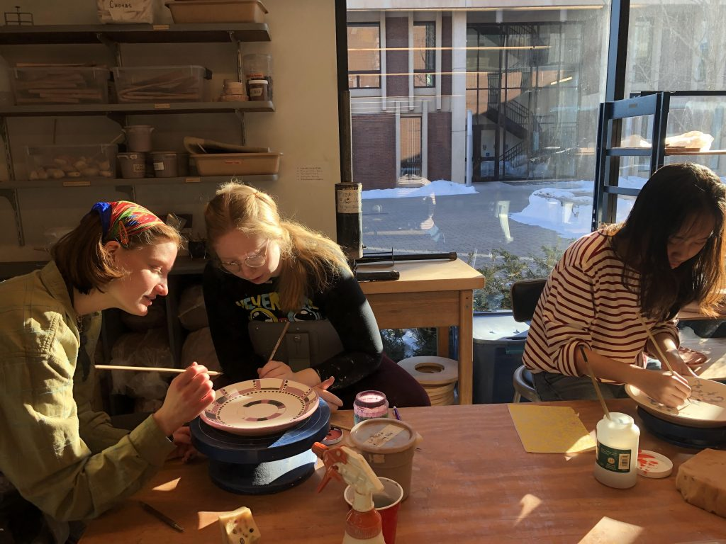 Grace Jones '22, Lana Berry '22, and Zoey Pham '23 decorate bowls thrown by the late art professor, Gary Erickson, during an Empty Bowls workshop on Feb. 8, 2020. Photo taken by Norah Ntagungira.