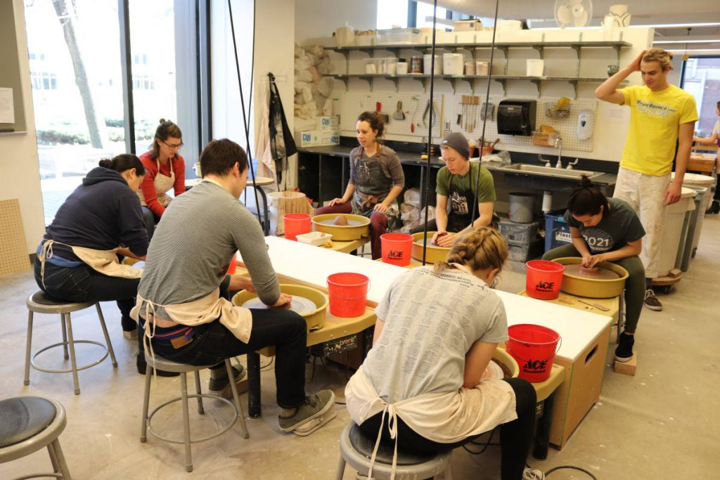 Students throwing pots at the wheels in the Margaret H. Soltis Ceramics Studio. (Photo by Nicolas Koch-Gallup)