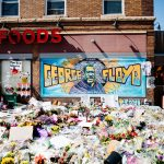 Image shows George Floyd's memorial in front of Cup Foods on Lake Street. In front of a colorful mural of George Floyd, hundreds of colorful flowers and community art recognizing Floyd's life are laid.