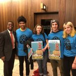 Three Macalester students stand next to Mayor Carter (mayor of Saint Paul), holding signs that promote a fifteen dollar minimum wage.