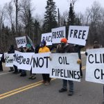 Protesters hold signs near a proposed Line 3 pipeline route.