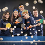 five students posing with ping pong paddles and balls