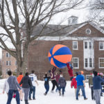 Students pushing a 6ft blue and orange ball in the air