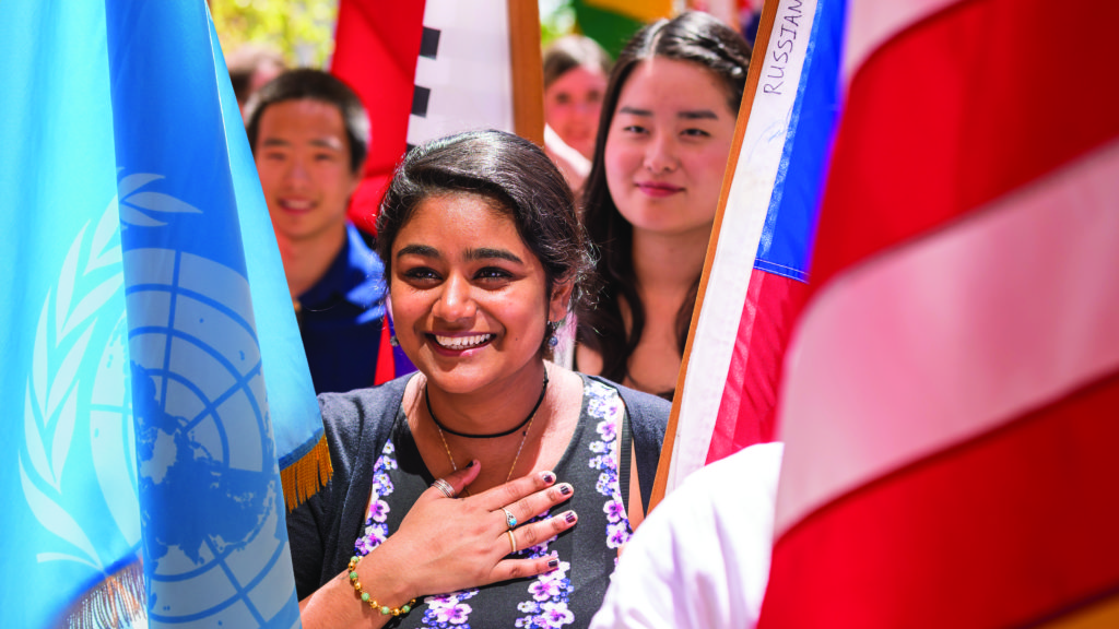 Students carry flags for the countries represented in the first year class during Orientation