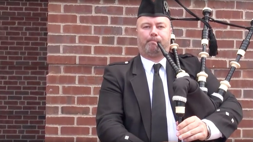 Mike Breidenbach '96 playing bagpipes.