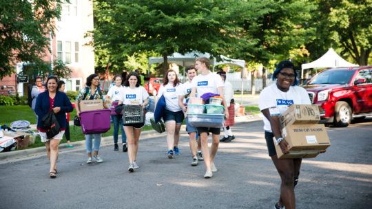 Orientation leaders help first year students move in.