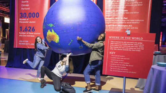 Image of students holding globe
