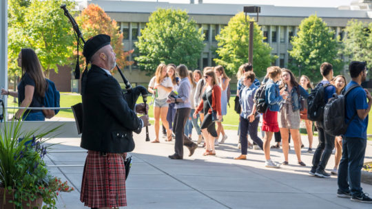 Photo of a piper playing as students enter a building.