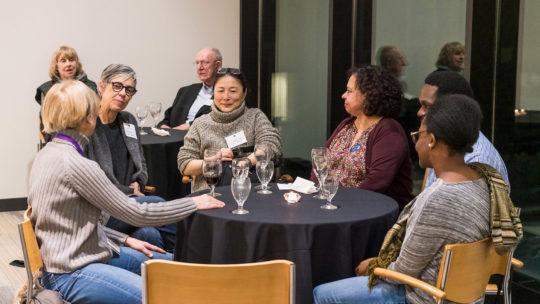 Photo of alumni gathered around a table