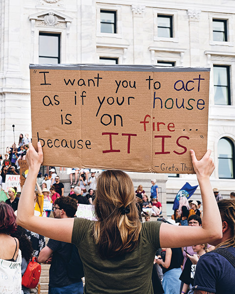 "Photo of a Macalester student holding a sign reading ""I want you to act as if your house is on fire... because IT IS - Greta Thunberg"""