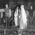 Photo of ten students dressed in Shakespearean costumes on a stage.