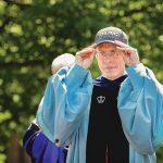 "President Rosenberg wearing a ""Mac Alumni"" baseball cap"