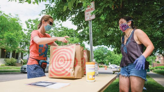 Photo of a donor placing bags of food on a table in front of a volunteer (both wearing masks)