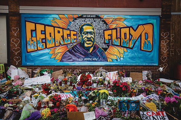 Photo of a mural of George Floyd with flowers laid in front of it