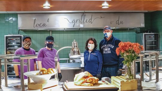 Photo of President Rivera and her spouse standing with two Bon Appetit workers behind a roasted turkey (all are masked)