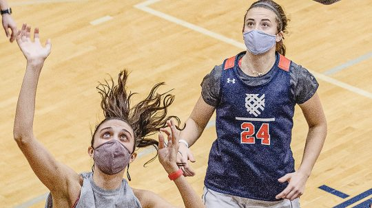 Photo of two students wearing masks and playing basketball