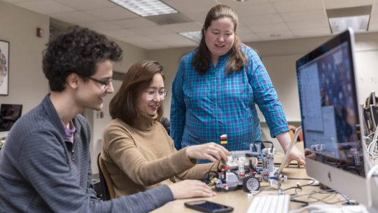 Photo of Susan Fox watching two students build a robot