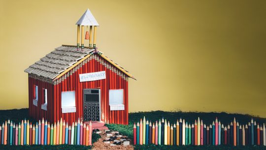 Photo illustration of a schoolhouse made of colored pencils